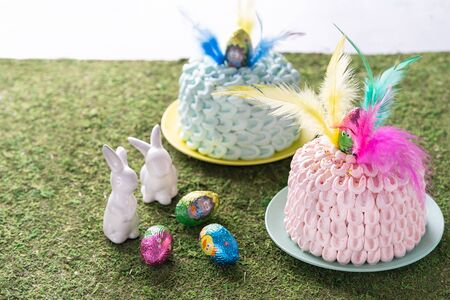 Mona de pascua, a pink and blue cakes eaten in Spain on Easter Monday, decorated with a chocolate egg and feathers of different colors. Easter decoration, selective focus. Space for text.
