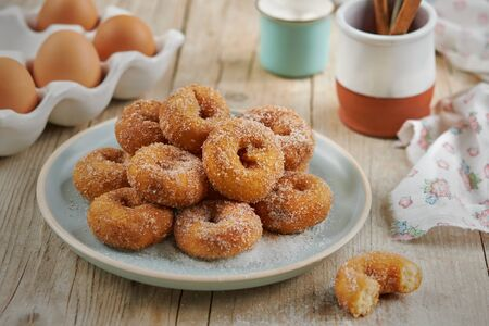 Closeup of a pile of homemade Doughnuts of easter, rosquillas, traditional anise donuts from Spain, typically eaten in Easter, on a rustic wooden table. Mediterranean sweet food concept. Banco de Imagens