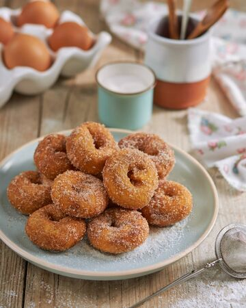 Closeup of a pile of homemade Doughnuts of easter, rosquillas, traditional anise donuts from Spain, typically eaten in Easter, on a rustic wooden table. Mediterranean sweet food concept.