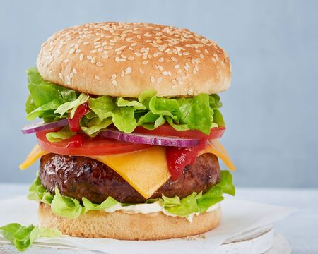Close-up of a tasty hamburger sandwich containing: cooked patties of ground meat, onion, tomatoes, cheese, sauce fresh green salad on a light background, copy space. Fast food and barbecue collection. Horizontal.