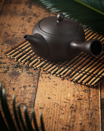 Traditional japanese ceramic brown teapot, on bamboo tray over wooden dark background, vintage effect. Selective focus.