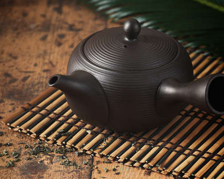 Kyusu, small teapot used in making Japanese green tea on wooden background. Wabi sabi concept, selective focus, minimalism. Imagens