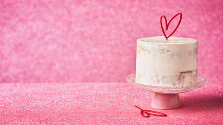 Close Up of a White Cake decorated with heart cake topper, against a pink glossy background, copy space. Romantic love concept. Valentine's, Mother's Day, Birthday Cake card Banner. Horizonlal.