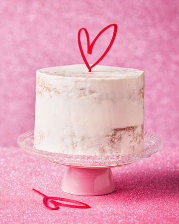 Close Up of a White Cake decorated with heart cake topper, against a pink glossy background. Romantic love concept, Valentine's, Mother's Day, Birthday Cake card.