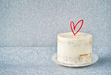 White Cake decorated with heart cake topper, against a gray blue glossy background, copy space. Romantic love concept. Valentine's, Mother's Day, Birthday Cake card Banner, selective focus.
