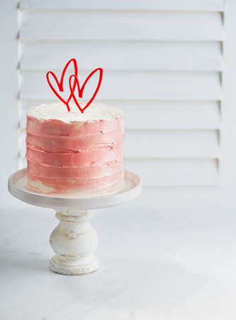 Buttercream layer cake decorated with heart cake toppers, against a white background with space for text. Romantic love concept. Valentine's, Mother's Day, Birthday Cake card Background. Imagens