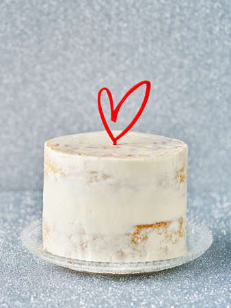Valentine's buttercream White Cake decorated with heart cake topper, against a gray blue glossy background, copy space. Romantic love concept. Mother's Day, Birthday Cake card Banner, selective focus.