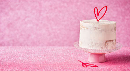 White Cake decorated with heart cake topper, against a pink glossy background bannner, copy space. Romantic love concept. Valentine's, Mother's Day, Birthday Cake card Banner. Selective focus.