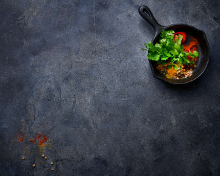 Food concept ingredients background, fresh coriander turmeric, cayenne red pepper species, coriander grains iron tray on dark textured surface, empty copy space.