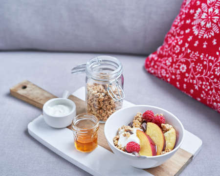 Healthy breakfast concept, natural yogurt with raspberries and nectarines, honey and muesli on a kitchen table. Nutrition. Selective focus, copy space.