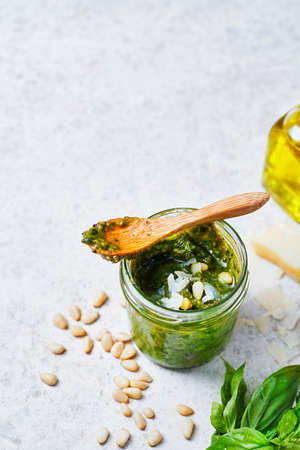 Green Pesto Sauce with Ingredients, Fresh Basil, Pine Nuts, Garlic and Cheese on light brown background, Copy space for your text, Selective focus. Healthy food concept. Imagens