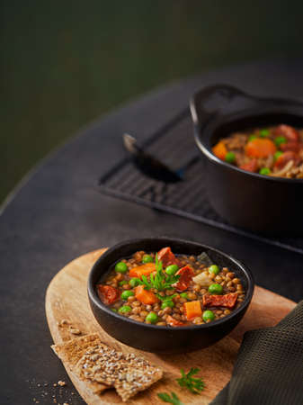 Lentil stew in bowl with vegetables, parsley chorizo spanish soup on a dark green background, space for text. Selective focus. Mediterranean healthy food concept.
