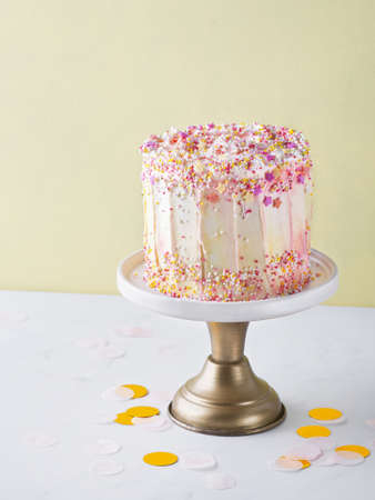 Yellow buttercream ombre birthday cake with colorful sprinkles over yellow background with copy space. Romantic love concept. Valentine's, Mother's Day, Birthday Cake card Background, Close Up.