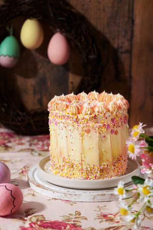 Beautiful composition with Easter fun cake decorated with sprinkles on a wooden background, space for text. Romantic vintage style. Spring station concept.