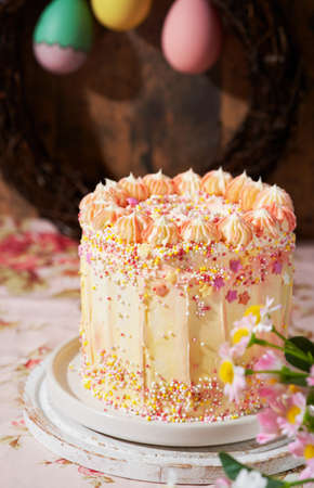 Easter fun cake decorated with sprinkles on a wooden background, space for text. Romantic vintage style. Spring station concept.