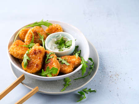 Vegetarian Nuggets with Vegan Dipping Sauce and rocket leaves on a light background with space for text, selective focus. Healthy Diet, Protein Vegetarian Meals concept, alternative meat products.