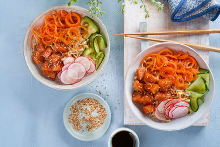 Noodles with vegetables, marinated salmon Sashimi, Carrot noodles, cucumber, radish soy sauce, sesame seeds, poke bowls, light background, copy space. Top view, overhead. Healthy clean eating concept. Imagens