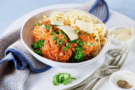 Meatballs with spaghetti, tomato sauce, parmesan cheese crumbles, broccolini, broccoli florets, vegan healthy dinner, lunch on light blue background. Selective focus. Close-up.