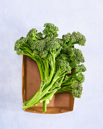 Raw broccolini, fresh organic broccoli florets green vegetable baby broccoli in paper box for storing food Plastic-free packaging, zero west concept. Light blue background, copy space.