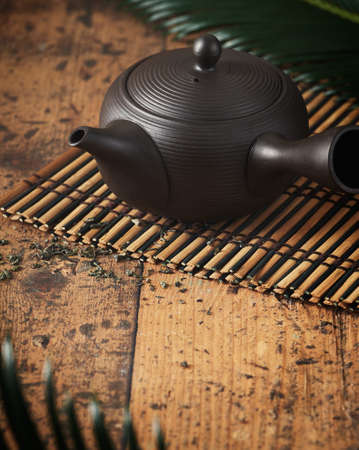 Teapot, Kyusu, small used in making Japanese green tea on wooden background with copy space. Wabi sabi concept, selective focus, minimalism.