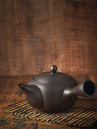 Traditional japanese ceramic brown teapot, on bamboo tray over wooden dark background, copy space, vintage effect. Selective focus. Wabi sabi concept.