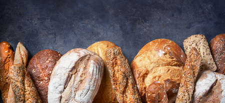 Banner with Different Types of Bread on dark surface. Close up. Bakery concept. Empty space for text. Food bakery shop concept background. Imagens