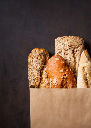 Assortment of baked bread, Crusty French Baguette, brown and white wheat grain loaves, seeds in crafting the package on a wooden brown surface. Top view. Bread bakery background. Copy space. Imagens