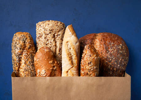 Bread bakery background. Assortment of baked bread, Crusty French Baguette, brown and white wheat grain loaves in crafting the package on a Blue classic background. Copy space. Top view. Imagens