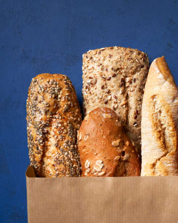 Assortment of baked bread, Crusty French Baguette, brown and white wheat grain loaves, seeds in crafting the package on a Blue classic background. Copy space. Top view. Close Up.