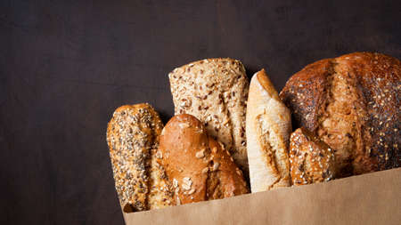 Assortment of baked bread brown and white wheat grain loaves in crafting the package on a wooden brown surface. Top view. Bread bakery background. Copy space. Imagens