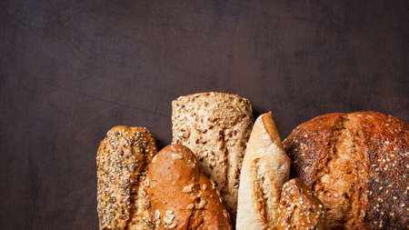 Variety breads with seeds in a brown kraft paper wrapper on a dark wooden surface with copy space. Bakery concept. Vertical Food bread background.