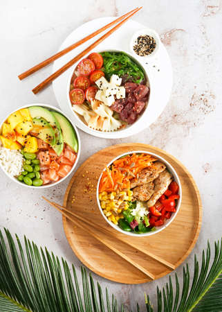 Asian salmon, tuna, heura soy protein or vegan chicken poke bowls with variety vegetables, served in bowl on tropical leaves. Marble table, Top view. Copy space. Fast healthy lunch, nutrition concept.