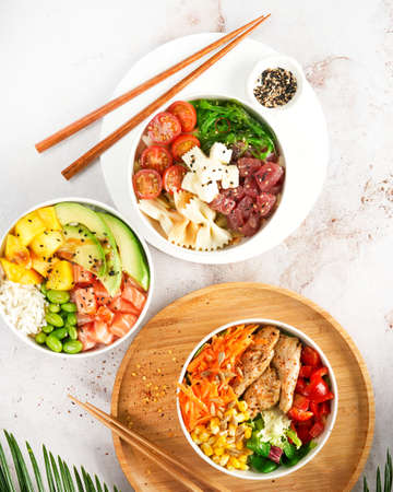Asian trendy poke bowls with salmon, tuna, heura soy protein vegan chicken, variety vegetables, served in bowl on tropical leaves. Protein Vegetarian Meals concept. Healthy delicious vegan food. Diet.