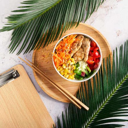 Healthy Vegan Poke bowl raw salad, heura vegetable protein, vegan chicken with variety vegetables, served in bowl on tropical leaves. Copy space. Top view. Healthy lunch, vegetarian restaurant menu.