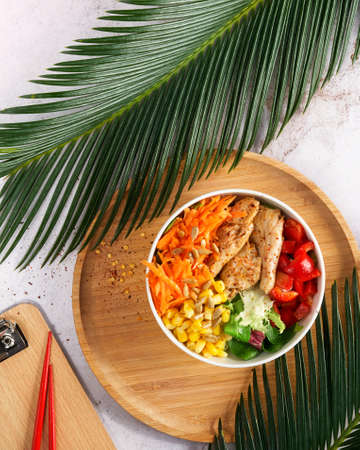 Vegan Poke bowl raw salad, heura soy protein, vegan chicken with variety vegetables, served in bowl on tropical leaves. Top view. Copy space. Fast healthy lunch, asian trendy food. Nutrition concept,