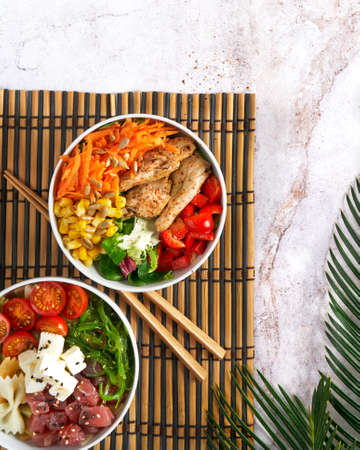 Hawaiian trendy poke bowls, tuna, heura soy protein or vegan chicken, variety vegetables, served in bowl on tropical leaves. Marble table, Top view. Copy space. Fast healthy lunch, nutrition concept. 写真素材