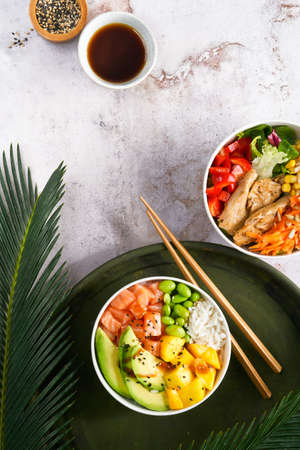 Hawaiian trendy poke bowls with salmon, heura soy protein or vegan chicken, variety vegetables, mango served in bowl on tropical leaves. Marble table, Top view. Healthy Nutrition concept. Copy space.