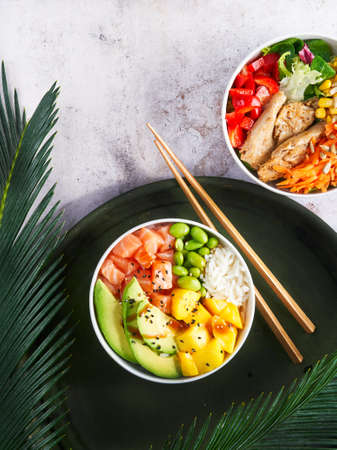 Hawaiian trendy poke bowls, salmon, heura soy protein or vegan chicken, variety vegetables, served in bowl on tropical leaves. Marble table, Topview. Fast healthy lunch, nutrition concept. Copy space.