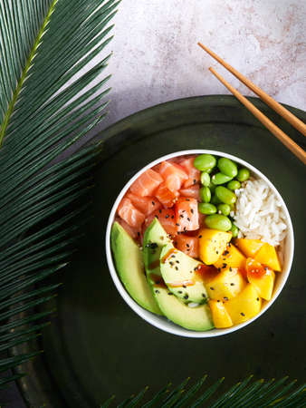 Salmon Poke bowl Raw fish salad Asian trendy food, mango, soy beans edamame, rice, avocado, served in bowl on tropical leaves. Marble table, top view. Copyspace. nutrition concept, fast healthy lunch. 写真素材
