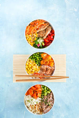 Healthy fast dish, Three Poke bowls flamed salmon, pulled pork, vegan protein alternative heura, variety vegetables, rice, noodles, ramen. Turquoise surface. Copy scape. Hawaiian dish, nutrition concept. 写真素材
