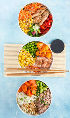 Three Poke bowls flamed salmon, pulled pork, vegan protein alternative heura, variety vegetables, rice, ramen. Turquoise surface. Copy scape. Hawaiian dish. Fast healthy lunch, nutrition concept.