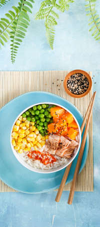 Food banner Poke bowl flamed salmon, rice, pumkin, green peas, sweetcorn, sesame seeds. Turquise surface. Trendy asian food, Copy space. Fast healthy lunch, nutrition concept. Top view.