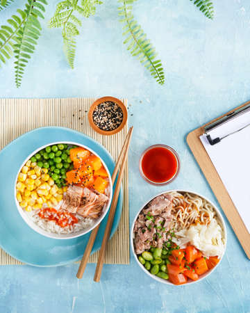 Fast healthy lunch, Poke bowls flamed salmon, pulled pork, rice, noodles, baek kimchi, pumkin green peas, sweetcorn, sesame seeds. Turquise surface. Trendy food, Copy space. Top view, restaurant menu. 写真素材 - 165676391