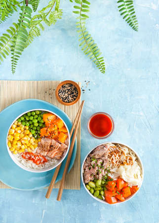 Poke bowls flamed salmon, pulled pork, rice, noodles, fermented cabbage, pumkin green peas, sweetcorn, sesame seeds. Turquise surface. Trendy food, Copy space. Top view. Healthy lunch restaurant menu. 写真素材