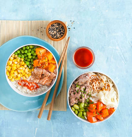 Fast healthy lunch, two poke bowls flamed salmon, pulled pork, rice, noodles, fermented cabbage, pumkin green peas, sweetcorn, sesame seeds. Trendy asian food, copy space, nutrition concept. Top view.