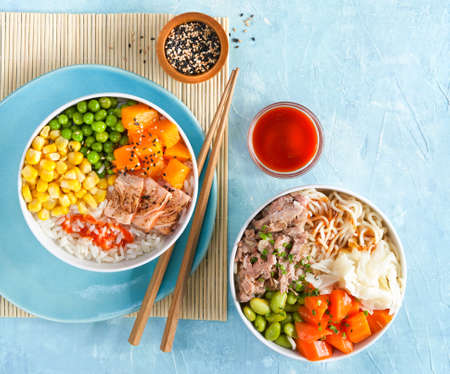 Two poke bowls flamed salmon, pulled pork, rice, noodles, fermented cabbage, pumkin green peas, sweetcorn, sesame seeds. Trendy asian food, Copy space. Fast healthy lunch, nutrition concept. Top view, 写真素材
