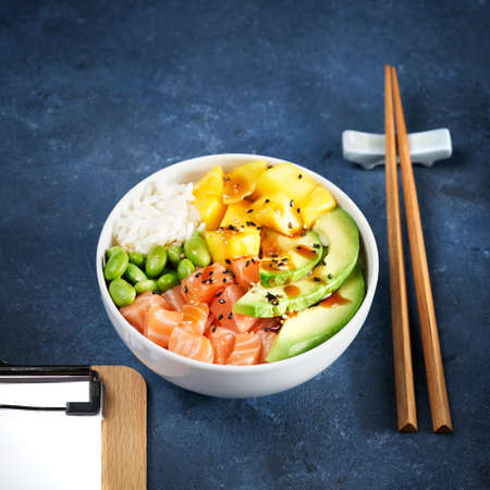 Fast healthy lunch, Salmon Poke bowl Raw fish salad Asian trendy food, mango, soy beans edamame, rice, avocado, served in bowl on tropical leaves. Marble table, Copy space. Selective focus. 写真素材