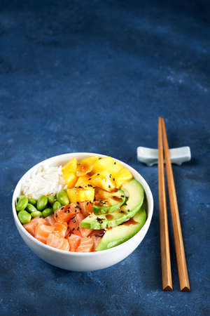 Salmon Poke bowl Raw fish salad Asian trendy food, mango, soy beans edamame, rice, avocado, served in bowl, chopsticks, blue dark background. Copyspace. nutrition concept, fast healthy lunch.