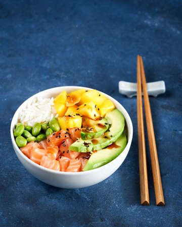 Healthy and clean eating concept. Salmon Poke bowl Raw fish salad, mango, soy beans edamame, rice, avocado, served in bowl, chopsticks, blue dark background. Copy space. Selective focus. 写真素材 - 165395016