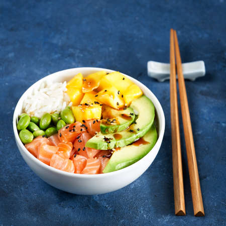 Salmon Poke bowl Raw fish salad Asian trendy food, mango, soy beans edamame, rice, avocado, served in bowl, chopsticks, blue dark background. Copy space, healthy lunch. Selective focus.